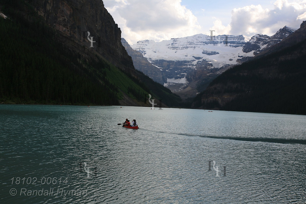 Tourists paddle canoes across Lake Louise beneath soaring mountains of Banff National Park in the Canadian Rockies; Alberta, Canada.