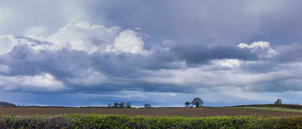 Towering Cumulus and Stratocumulus storm clouds in cloud formation in springtime at Swinbrook in the Cotswolds, Oxfordshire, UK