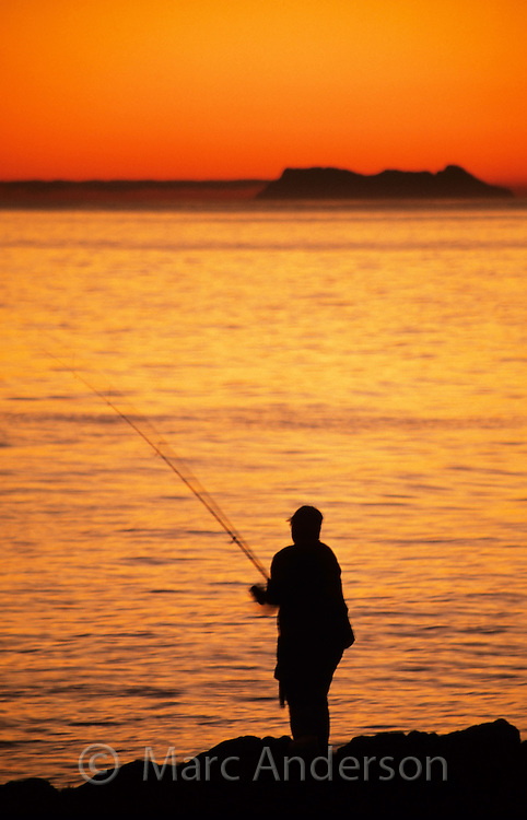 Silhouette of a fisherman at sunset with Gibraltar in the background, Marbella, Costa Del Sol, Spain