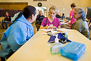 08 DECEMBER 2010 - PHOENIX, AZ: MICKEY IARRABEE (right) a volunteer translator, works with MARIA GARCIA (left) who was seeing ELIZABETH OSBORN, a volunteer nurse,at a Mission of Mercy mobile clinic in Phoenix, AZ, Wednesday, Dec. 8. Mission of Mercy has been providing free medical help for people in the Phoenix area since 1997. In the last two years, as the Arizona economy continued its recessionary slide, patient load at the clinics has more than doubled. Mission of Mercy, which relies on voluntary medical help and financial donations, recently acquired another mobile clinic so they could expand their reach into suburban areas they previously had not served. Mission of Mercy has provided free medical help to more than 43,000 patients in the Phoenix area since 1997.    PHOTO BY JACK KURTZ