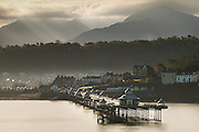 Sun rays over the Welsh mountains of Snowdonia with Bangor Victorian Pier in the foreground, jutting into the Menai Strait. Bangor is a University town and is now almost utterly dependent on the University for the city's economy.