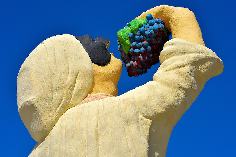 Chief Eating Grapes Statue in Palm Beach District, Aruba<br /> This statue of a man wearing a toque (chef&rsquo;s hat), a theater mask and eating grapes symbolizes the plethora of restaurant options available in Palm Beach. The cuisine and price ranges can accommodate any palate and budget. Entertainment selections are equally varied, from quiet bars to rocking clubs and ten casinos. The two best retail experiences are the Palm Beach Plaza, an enormous mall, and the Paseo Herencia, a more casual shopping environment.
