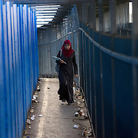 A Palestinian students make her way out early in the morning at the checkpoint 300, the crossing passage between Bethleem and Jerusalem, on December 15. 2010 in Bethleem. Workers arrived every day at two o'clock in the morning  to catch a place at the entrance of the checkpoint, so they can arrived at time to their work in the Israeli side. Photo by Olivier Fitoussi