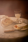 Tabletop setting of absinthe, brie cheese, orange jelly and French bread. A delicious pairing.