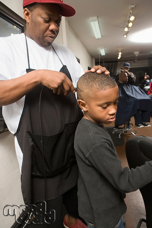 A young boy having his hair shaven in the barbers