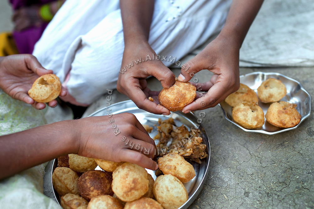 Poonam, 10, (right) and her sister Jyoti, 11, (left) are eating Panipuri, a typical Indian street snack, while sitting in the front yard of their newly built home in Oriya Basti, one of the water-contaminated colonies in Bhopal, central India, near the abandoned Union Carbide (now DOW Chemical) industrial complex, site of the infamous '1984 Gas Disaster'.