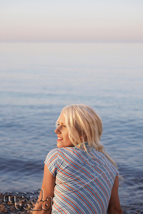 Young woman sitting on beach back view
