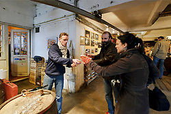BRUSSELS, BELGIUM - DEC-30-2010 -  Jean Van Roy, the fourth generation owner of the Brasserie Cantillon, left, offers a sample of Gueze to Stephane Chabert, center, and Yaele Vigouroux, both of Savoie, France. Cantillon is a working brewery and museum of Belgian beer history. Cantillon specialises in a unique, wine-like style of beer called Lambic in its most elemental form, and Gueze when it's blended. The sour beer gets its funky, acidic bite from a spontaneous fermentation process and long aging that inoculates the wort, or pre-beer, with bacteria and yeast naturally available in the air. Variations include batches aged with cherries (Kriek), raspberries (Rose de Gambrinus), and apricots (Fou'Foune), all produced organically and all 100 percent Lambic. (Photo © Jock Fistick)
