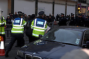 London 04/01/09: Protests outside the Israeli Embassy in London UK: A protester is led through London traffic and shoppers after a scuffle with police