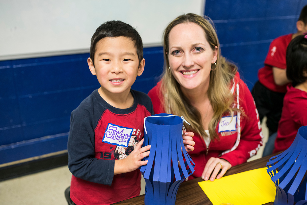 Jayson and Jennifer Connelly make a paper lantern at the craft table during a lunar new year event hosted by Families Through Korean Adoption (FTKA) in the gym and school cafeteria of St. Dennis Church in Madison, Wis., on Feb. 10, 2018. The event celebrated the passing of the lunar new year, and is one of several events for FTKA-member families and children to gather and enjoy cultural fun, food and play. (Photo by Jeff Miller - www.jeffmillerphotography.com)