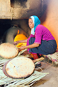Lady prepares madfouna - the Berber pizza - at a earthen home in Aoufouss village, Southern Morocco, 2015-06-09.