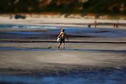 candid action: boy playing on beach, dragging a buoy found on the shoreline,  Kangaroo Island, South Australia, Australia