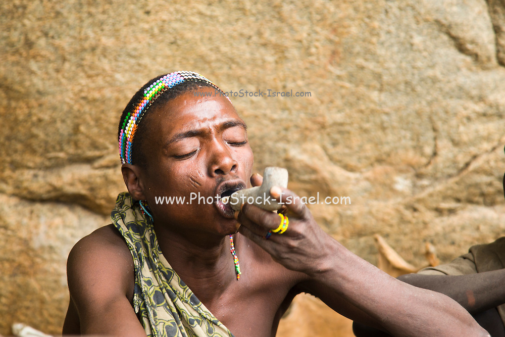 Hadza hunter smokes a clay pipe. The Hadza, or Hadzabe, are an ethnic group in north-central tanzania, living around Lake Eyasi in the Central Rift Valley and in the neighboring Serengeti Plateau.
