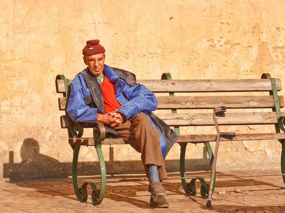 Elderly Moroccan man sits in the sun outside the Old Medina in Casablanca.