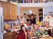 (MODEL RELEASED IMAGE). The Caven family in the kitchen of their home in American Canyon, California, with a week's worth of food. Craig Caven, 38, and Regan Ronayne, 42 (holding Ryan, 3), stand behind the kitchen island; in the foreground is Andrea, 5. Cooking methods: electric stove, microwave, outdoor BBQ. Food preservation: refrigerator-freezer, freezer. Favorite foods? Craig: beef stew. Regan: berry yogurt sundae (from Costco). Andrea: clam chowder. Ryan: ice cream. /// The Caven family is one of the thirty families featured in the book Hungry Planet: What the World Eats (p. 260). Food expenditure for one week: $159.18 USD. (Please refer to Hungry Planet book p. 261 for the family's detailed food list.)