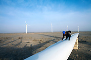 Gansu, China - 26 Feb 2010. A maintenance worker marks a blade of a windmill at Guazhou wind farm near Yumen, Gansu province, China. China has set a target for renewable energy consumption of 40 percent of the market by the year 2050.