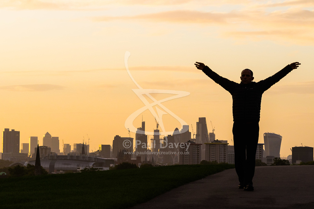 London, September 11 2017. A man exercises against the backdrop of the London skyline as a new day breaks over the city. © Paul Davey