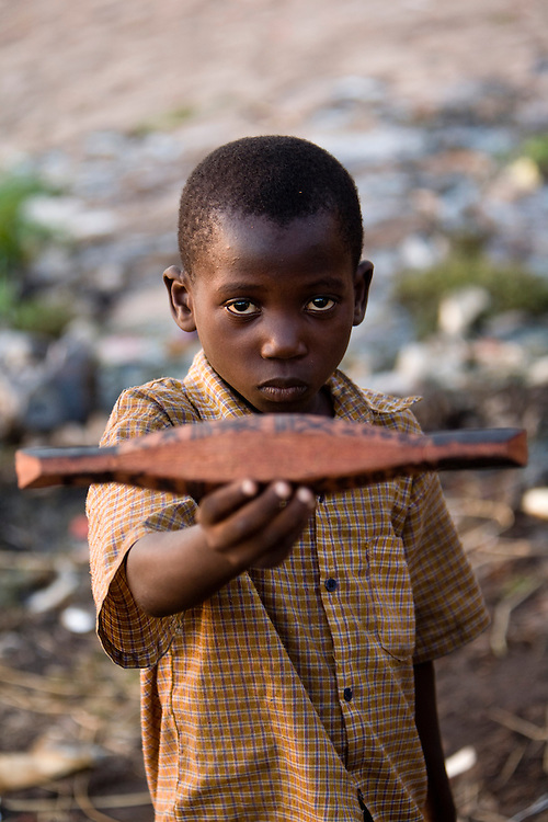 """A boy shows a miniature """"pinasse"""", the tipical canoe from the regions. At the confluence of the Niger and the Bani rivers, between Timbuktu and Segou, Mopti is the second largest city in Mali, and the hub for commerce and tourism in this west-african landlocked country."""