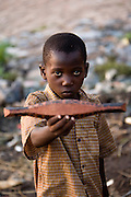 "A boy shows a miniature ""pinasse"", the tipical canoe from the regions. At the confluence of the Niger and the Bani rivers, between Timbuktu and Segou, Mopti is the second largest city in Mali, and the hub for commerce and tourism in this west-african landlocked country."