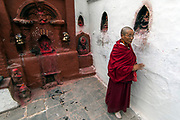 Pilgrim monk at Boudhanath buddhist stupa, centre of the tibetan community in Kathmandu