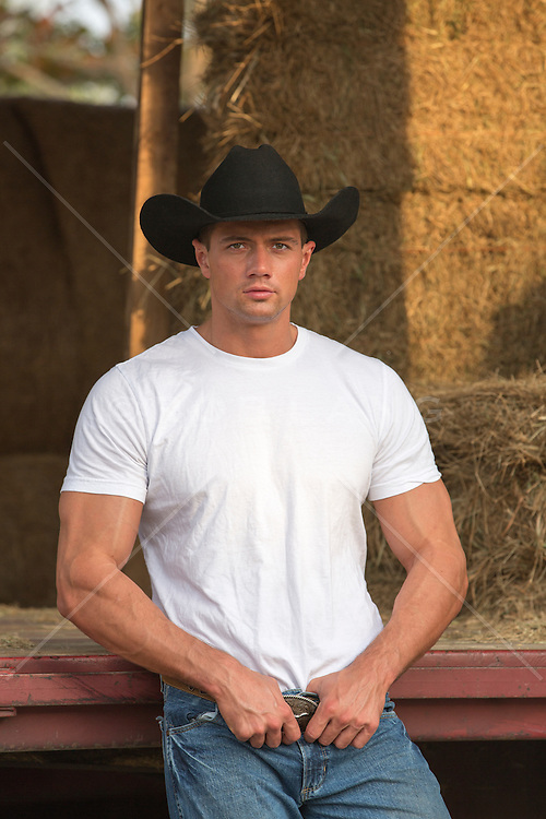 handsome cowboy near a truck loaded with hay bales