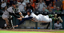 Houston Astros' George Springer, right, dives past Baltimore Orioles catcher Caleb Joseph (36) to score a run on Jose Altuve's RBI double during the first inning of a baseball game, Saturday, May 27, 2017, in Houston. (AP Photo/Eric Christian Smith)
