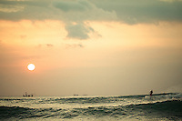 A surfer and a fishing boat linger in the sunset, Dreamland, Bali, Indonesia.