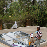 Three young Rwandan brothers gaze into one of the mass graves at the Kigali Memorial Centre in downtown Kigali, Rwanda.