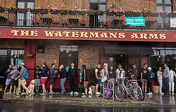 © Licensed to London News Pictures. 28/06/2020. London, UK. Pub goers enjoys a pint of takeaway beer at the Watermans Arms next to the River Thames in Barnes, South West London despite the wind and rain as temperatures plummet since last week as forecasters predict a breezy but sunnier week ahead. Last week, Prime Minister Boris Johnson announced that tourism and hospitality including pubs, restaurants and campsites can now reopen from next Saturday the 4th of July as well as reducing the 2 metre rule to 1. Photo credit: Alex Lentati/LNP