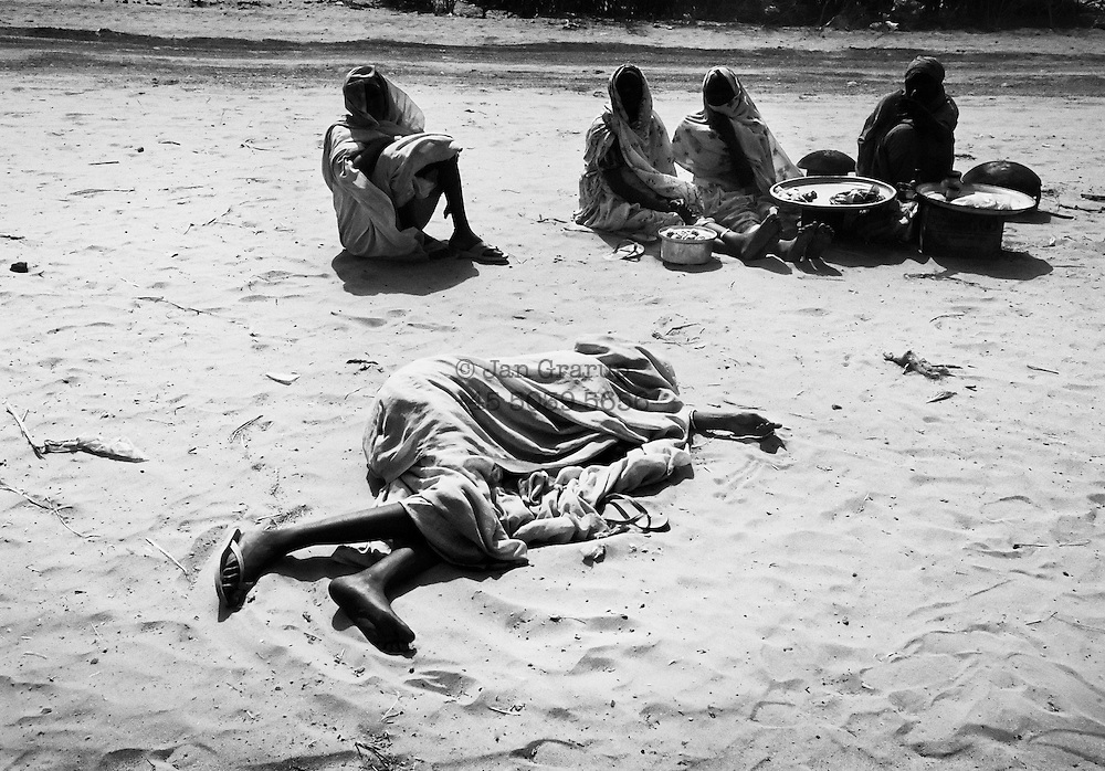 A young woman sick with malaria collapses in the camp. Passersby use her clothes to cover her and protect her from the burning desert sun. Meanwhile the woman lays helpless, waiting for someone to come to her aid... or to die.<br /> <br /> Kalma Camp, South Sudan - April 2005.