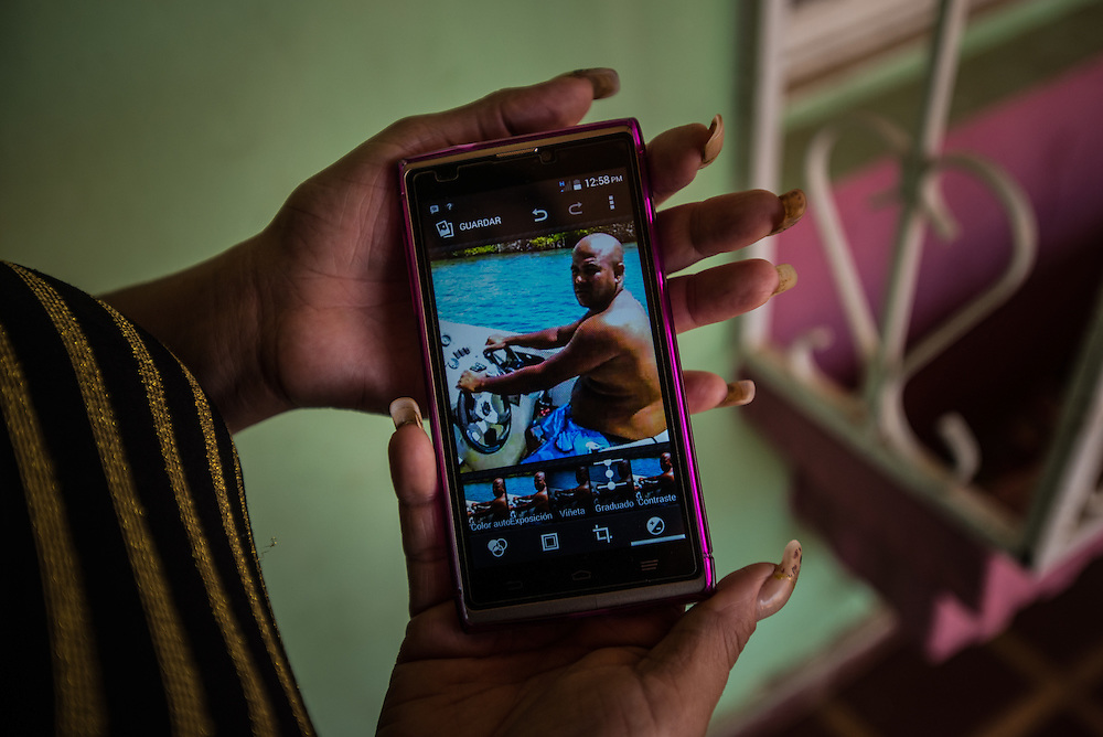 "LA VELA, VENEZUELA - SEPTEMBER 10, 2016: Saribeth Cordero shows visitors a cell phone photo of her missing  brother, William Cordero, who disappeared after leaving with a smuggler and other migrants to travel illegally by boat and look for work in Curaçao. This was one of the last photos he sent.  The plan had been a simple one: A seven-hour journey in a speedboat. If they were stopped by Curaçao's coast guard, they would pose as tourists. And with their documents in plastic bags, they were ready to swim ashore, knowing that the smuggler wanted to make a quick getaway. Then they could find their contacts using cell phones tucked in empty rice porridge jars. The migrants waited anxiously in La Vela for several days as the smuggler got reports from other fishermen in Curaçao about coast guard patrols, trying to decide which night would be safest to leave. Saribeth, recalled the group sitting in her brother's barber shop on her porch one afternoon as a movie played on the television about a shipwreck.""What if there are sharks?"" asked one of the migrants, Ms. Cordero recalled. ""You can't be negative like that,"" Mr. Cordero said, his sister recalled. But she said her brother was scared too. ""He was nervous about the ocean,"" Ms. Cordero said. PHOTO: Meridith Kohut for The New York Times"