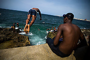 A teenager jumps off a concrete wall into the ocean along the Malecon avenue in Havana, Cuba on Saturday June 28, 2008.