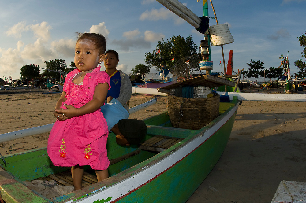 A young girl stands in her family's boat in one of the fish markets in Bali, Indonesia.