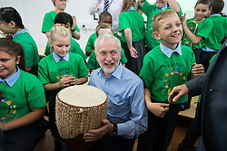 © Licensed to London News Pictures . 27/09/2016 . Liverpool , UK . Labour Party leader JEREMY CORBYN with a bongo drum during a visit to Faith Primary School in Liverpool , where he listens to and then joins in with the school orchestra . Photo credit : Joel Goodman/LNP