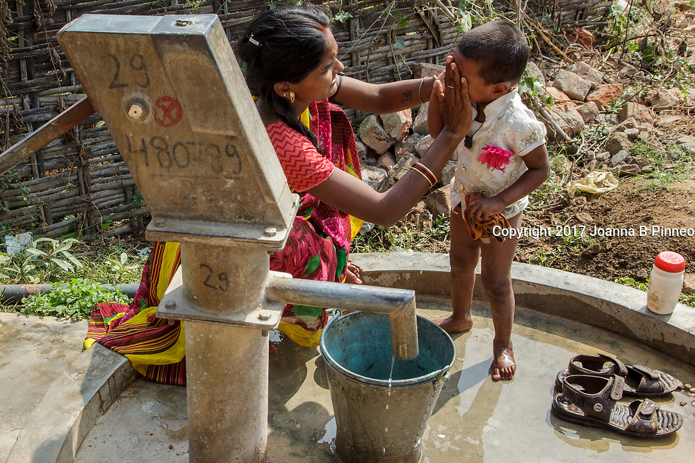 Harhori village, Sonbhadra, Uttar Pradesh, India. A mother washes her son using the water from a pump of water banned as drinking water. The red X on the pump indicates that the water is banned for drinking.