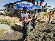 11 NOVEMBER 2014 - SITTWE, MYANMAR: A man carries his baby through a Rakhine Buddhist IDP camp near Sittwe. About 700 Rakhine Buddhist families live in an Internal Displaced Persons (IDP) camp on the edge of Sittwe. The people in the camp lost their homes in Sittwe in 2012 when Buddhist mobs rioted and burnt down Rohingya Muslim homes and businesses. The Buddhists' homes were mistakenly destroyed by other Buddhists or intentionally destroyed by retaliating Muslims during the 2012 violence. Unlike the Muslims, who live in much larger camps further from Sittwe, the Buddhists are allowed to come and go into downtown Sittwe and their homes are built in the traditional style, on stilts with large windows, and so are much more comfortable.   PHOTO BY JACK KURTZ