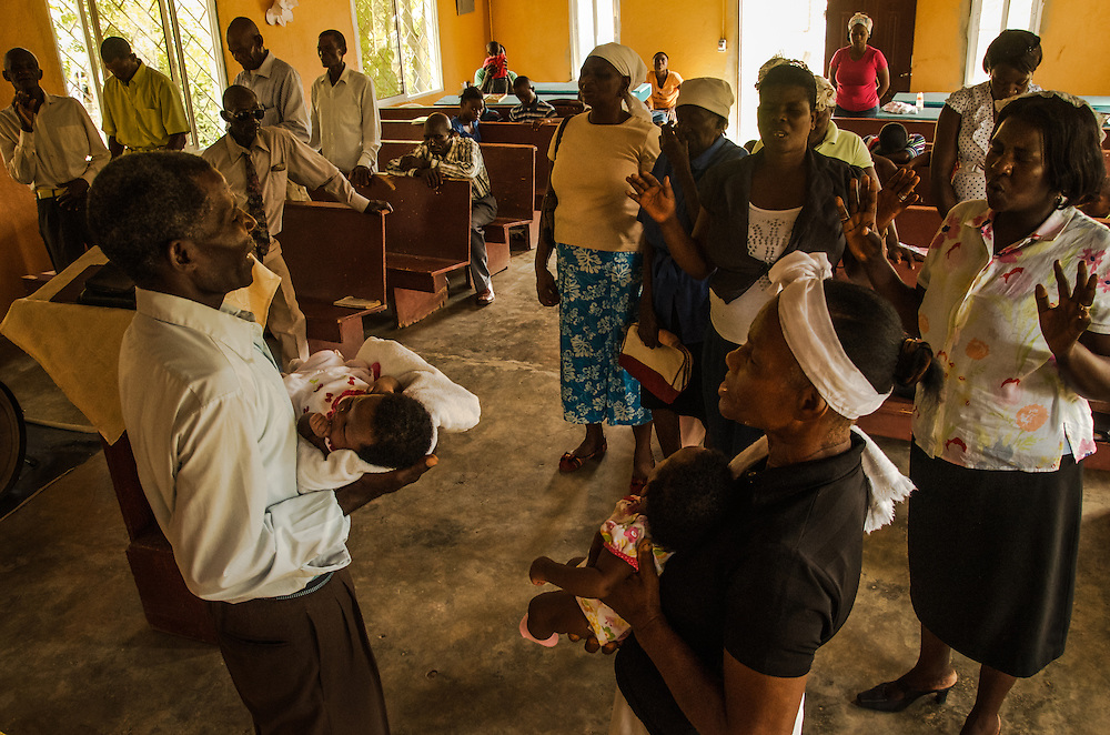 EL SEIBO, DOMINICAN REPUBLIC - OCTOBER 13, 2013: Luis Benitez, (left) blesses babies born in the Dominican Republic to parents also born in the Dominican Republic, to parents of Haitian descent, that have been denied birth certificates because of their grandparent's immigration status, during a Christian church service in an impoverished batey on a sugar cane plantation in El Seibo. Benitez led a Sunday church service in Creole for Haitian congregation members and their children, and led them in prayer asking God to help them to fight   judgment TC/0168, handed down by the Constitutional Court of the Dominican Republic.  The ruling essentially revokes Dominican citizenship from tens of thousands of people born in the Dominican Republic, which means they cannot have access to government services, id's necessary to travel and work, and the children cannot attend public school. The Inter-American Commission on Human Rights has expressed that the ruling would leave affected people stateless, which is a violation of the American Convention on Human Rights. During the service, the pastor discussed the idea of building a school for affected children so that they could continue their educations despite being denied birth certificates necessary for enrolling in public school.