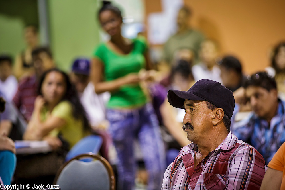 """18 AUGUST 2012 - PHOENIX, AZ: A man listens to immigration lawyers describe the deferred action program at a deferred action workshop in Phoenix. More than 1000 people attended a series of 90 minute workshops in Phoenix Saturday on the """"deferred action"""" announced by President Obama in June. Under the plan, young people brought to the US without papers, would under certain circumstances, not be subject to deportation. The plan mirrors some aspects the DREAM Act (acronym for Development, Relief, and Education for Alien Minors), that immigration advocates have sought for years. The workshops were sponsored by No DREAM Deferred Coalition.  PHOTO BY JACK KURTZ"""