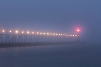 A foggy morning on Lake Michigan lends a desolate feeling to the pier and lighthouse in South haven, Michigan