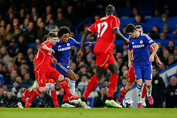 Willian of Chelsea is challenged by Alberto Moreno of Liverpool as he passes to Oscar of Chelsea - Photo mandatory by-line: Rogan Thomson/JMP - 07966 386802 - 27/01/2015 - SPORT - FOOTBALL - London, England - Stamford Bridge - Chelsea v Liverpool - Capital One Cup Semi-Final Second Leg.