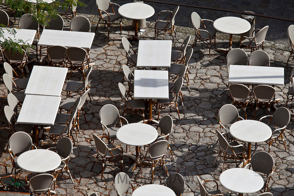 Empty tables at pavement cafe and cobbled pavement in St Emilion, Bordeaux region of France