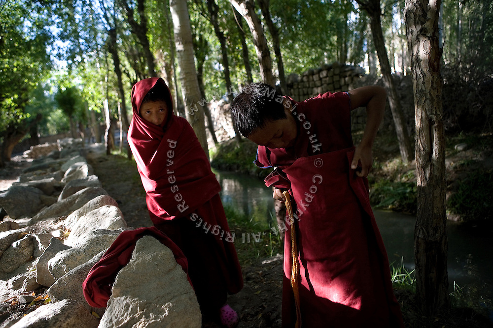 Two Buddhist novices dressing up after a bath in a nearby spring along of the Leh-Manali Highway.