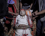 In Torajan culture, death is not necessarily the end.  The body of Lai' Tiku who passed on a few months ago is surrounded by her immediate family members in her home.  Her seated position signifies her high caste in the social ladder.  The matriarch in her family, Nenek Lai' Tiku passed away at age 102, she is survived by 10 children, 49 grandchildren, and 162 great-grandchildren.