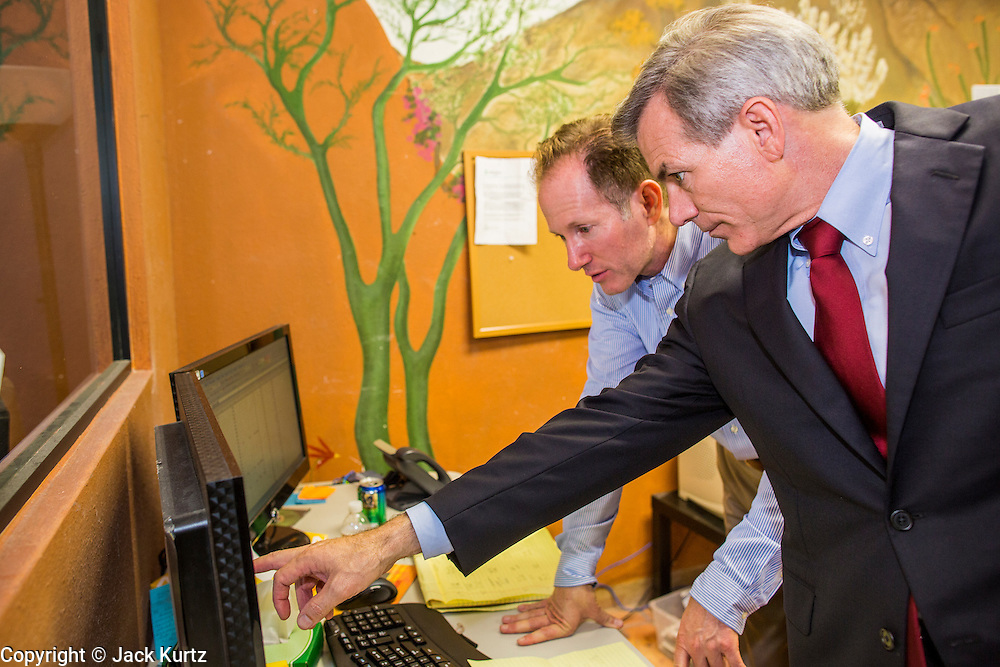 28 AUGUST 2012 - PHOENIX, AZ:  GREG PATTERSON (left, background) and Rep DAVID SCHWEIKERT (R-AZ), right, go over election results at Schweikert's campaign office Tuesday night. Schweikert faced Congressman Ben Quayle in what was the hardest Republican primary election in Arizona in 2012. Both were incumbent Republican freshmen elected to Congress from neighboring districts in 2010. They ended up in the same district at the end of the redistricting process and faced off against each other in the primary to represent Arizona's 6th Congressional District, which is made up of Scottsdale, Paradise Valley and parts of Phoenix. The district is solidly Republican and the winner of the primary is widely expected to win November's general election. Both are conservative Republicans with Tea Party backing.   PHOTO BY JACK KURTZ
