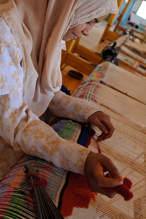 A woman weaving carpets at a co-op in Bashendi, Dakhla Oasis