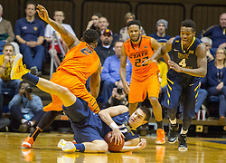 West Virginia Mountaineers guard Nathan Adrian (11) dives for a loose ball against the Oklahoma State Cowboys during the first half at the WVU Coliseum.