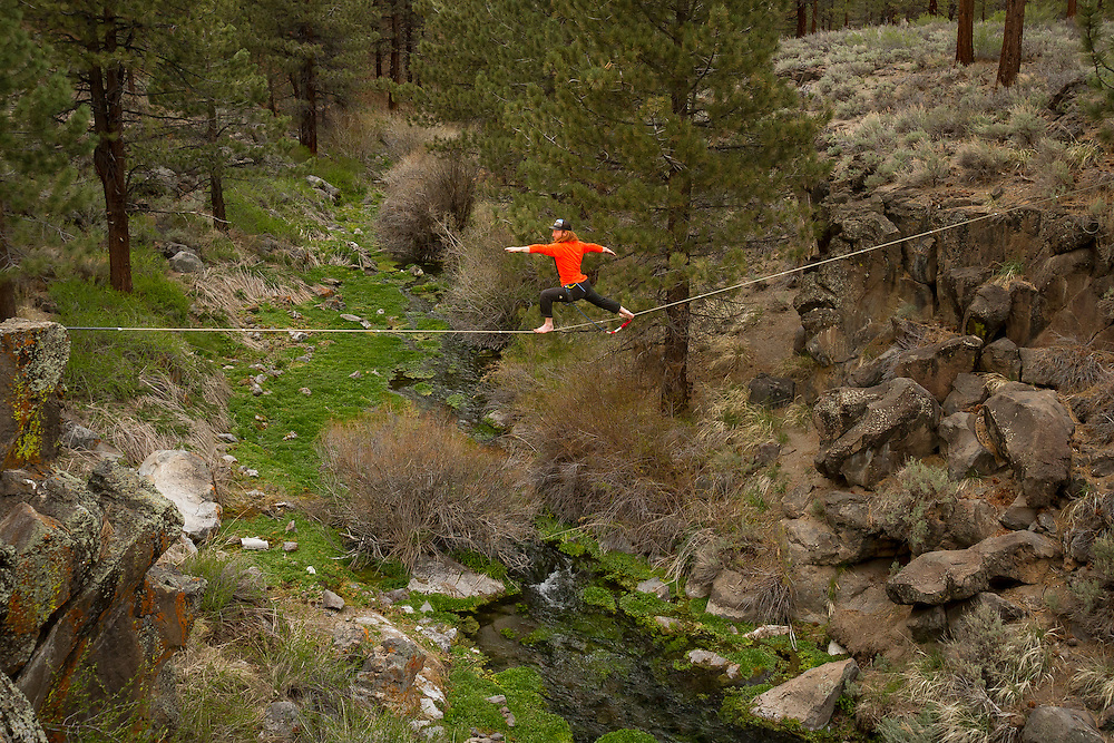 Scott Rogers holds a Warrior II pose on a mid line over a babbling creek.<br />