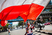 "09 MAY 2014 - BANGKOK, THAILAND: An anti-government protestor waves a Thai flag in the Ratchaprasong intersection of Bangkok. Thousands of Thai anti-government protestors took to the streets of Bangkok Friday to start their ""final push"" to bring the popularly elected of government of Yingluck Shinawatra. Yingluck has already been forced out by a recent court ruling that forced her to resign and she is facing indictment by the National Anti Corruption Commission of Thailand for alleged improprieties related to a government rice price support scheme. The protestors Friday were marching to demand that she not be allowed to return to politics. The courts have not banned her party, Pheu Thai, which has formed an interim caretaker government to govern until elections expected in July, 2014. Suthep Thaugsuban, secretary-general of the People's Democratic Reform Committee (PDRC),  said the president of the Supreme Court and the new senate speaker, who would be selected Friday, should set up an ""interim people's government and legislative assembly."" He went onto say that if they didn't, he would.     PHOTO BY JACK KURTZ"