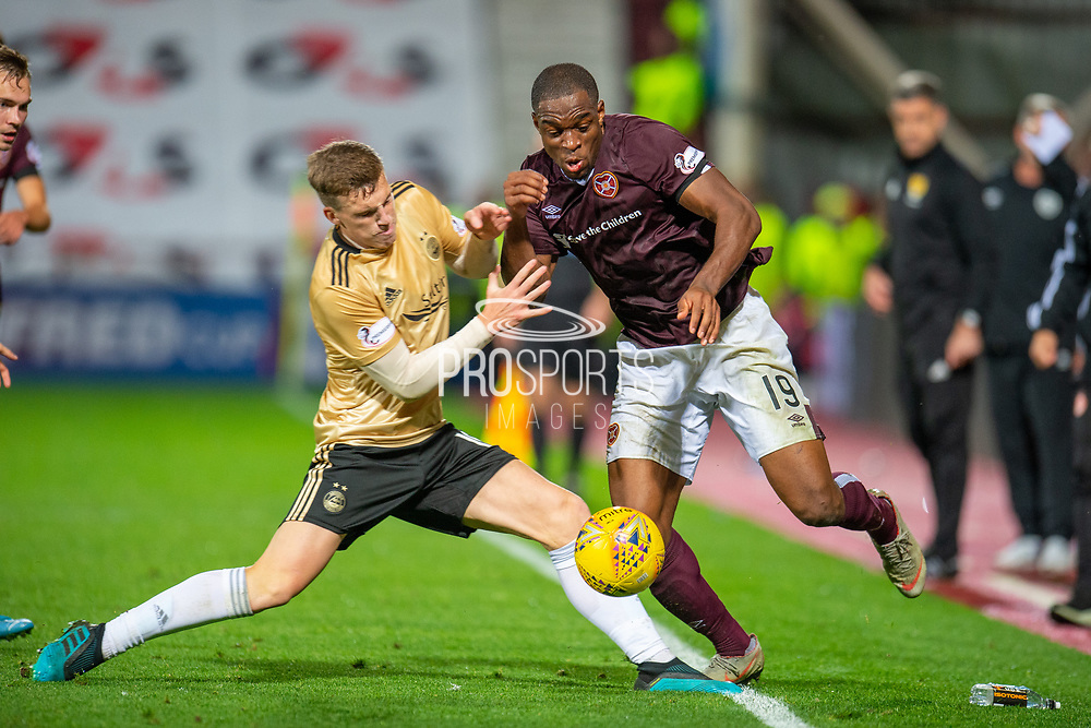 Lewis Ferguson (#19) of Aberdeen FC tackles Uche Ikpeazu (#19) of Heart of Midlothian FC during the Betfred Scottish Football League Cup quarter final match between Heart of Midlothian FC and Aberdeen FC at Tynecastle Stadium, Edinburgh, Scotland on 25 September 2019.