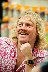 """Leigh Francis in character as TV JUICE host Keith Lemon poses for photos with fans while signing copies of his new book. 'Keith Lemon: The Rules""""  when he stopped in at WHSmith Meadowhall shopping centre in Sheffield. The event scheduled for 5:00 - 5:30 was so popular that Keith started signing early and didn't finish until 7:05pm as well as sales of the book being restricted.  .1st November 2011. Image © Paul David Drabble"""